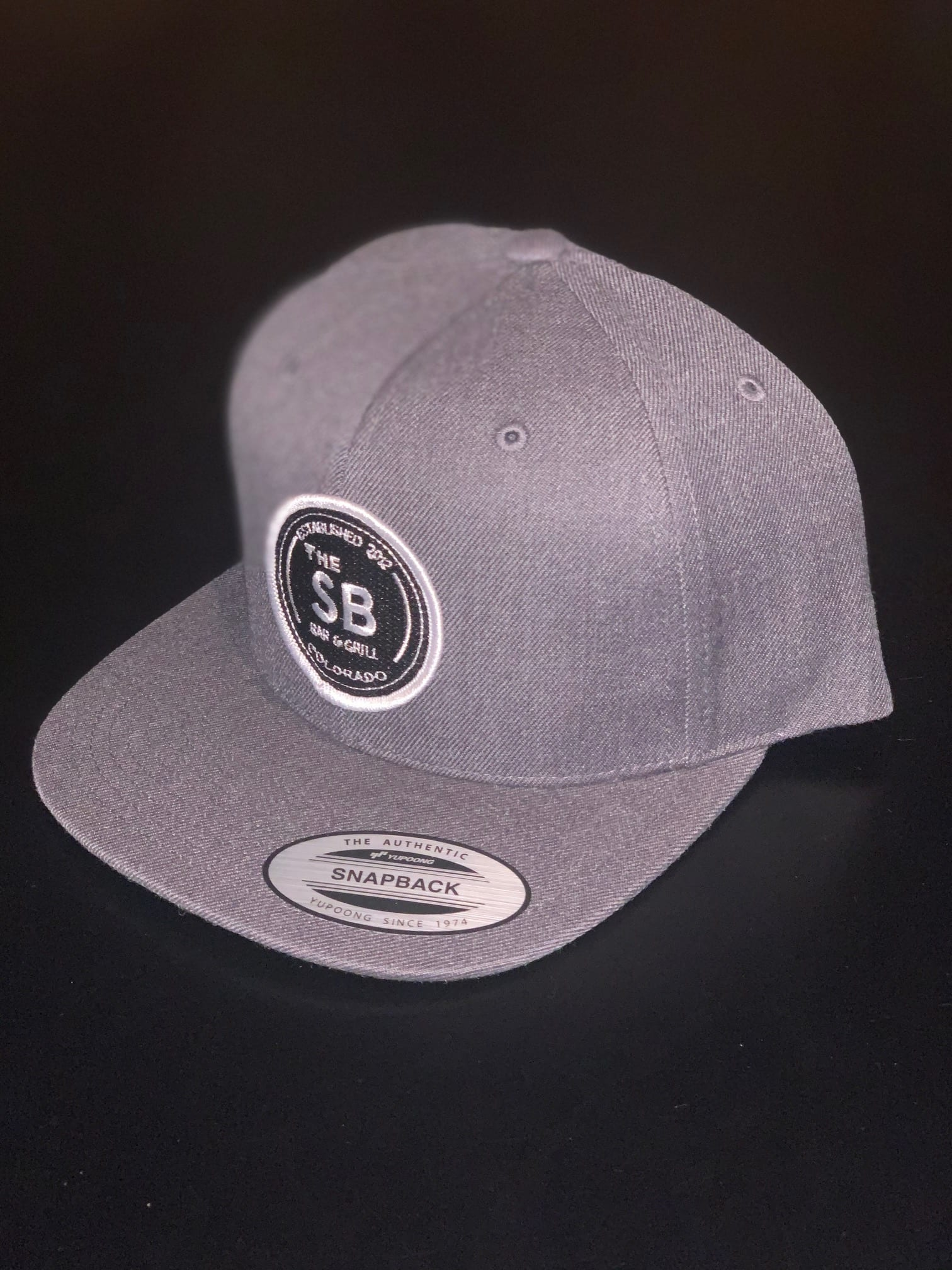 Grey snapback with black badge logo